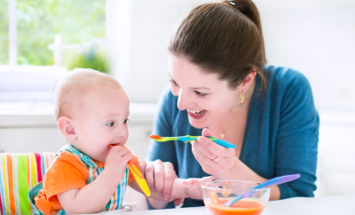 Young attractive mother feeding her cute baby son, giving him his first solid food, healthy vegetable pure from carrot with a plastic spoon sitting in a white sunny kitchen at a window at home