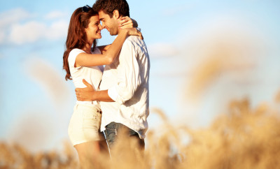 A young couple share an intimate moment while standing in a field