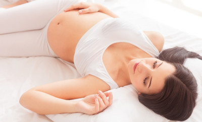 Beautiful young pregnant woman is napping in bed. She is lying and touching her tummy carefully