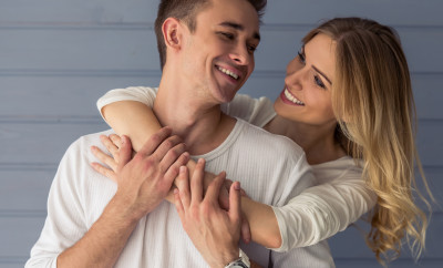 Portrait of beautiful young couple in casual clothes hugging, looking at each other and smiling, standing against gray wall