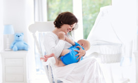 Mother and baby at home. Young woman holding her newborn child sitting in white rocking chair in sunny nursery with crib and garden view window. Parent and kid at home. Infant room interior.