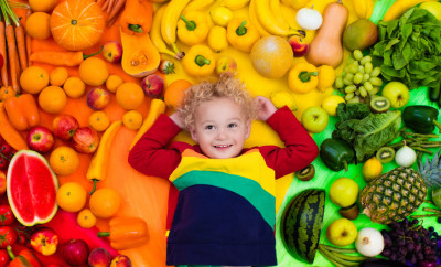 Baby boy with variety of fruit and vegetable. Colorful rainbow of raw fresh fruits and vegetables. Child eating healthy snack. Vegetarian nutrition for kids. Vitamins for children. View from above.