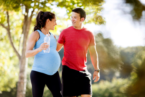 Pregnant woman with husband exercising.