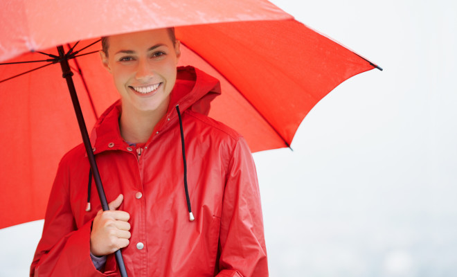A beautiful young woman standing outside while holding her red umbrella