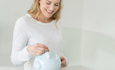 Happy woman saving money in a piggybank - home finances concepts