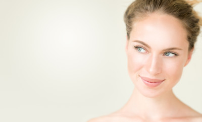 Beautiful natural woman smiling into copy space. Ambient light to underline the tender mood.