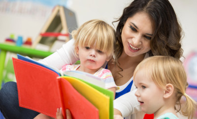 Hispanic young adult female teacher reading a colorful book to cute blonde toddler girls in a preschool classroom. They are sitting on the floor and looking at the book.