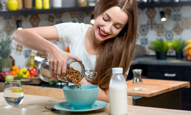 Young woman making breakfast with granola and milk in the modern kitchen at home