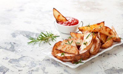 Roasted potato wedges with rosemary and tomato sauce, selective focus