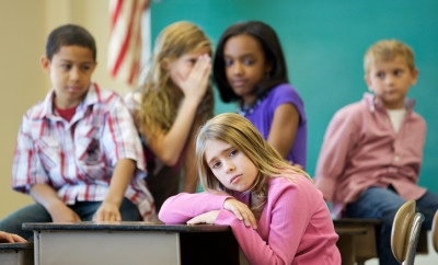 A young girl being bullied in a classroom setting.