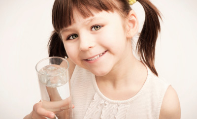 portrait of a little girl with a glass of water in hand