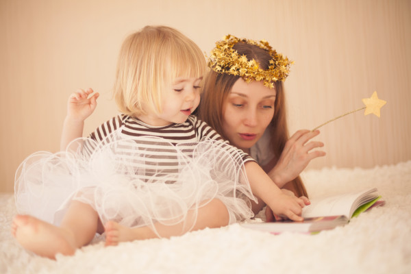 Mother and cute little girl reading in bed