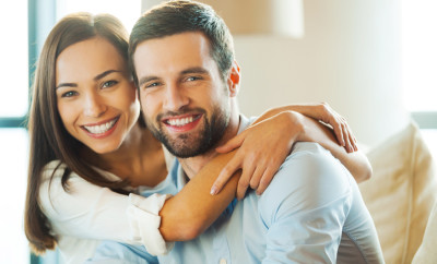 Beautiful young loving couple sitting together on the couch while woman embracing her boyfriend and smiling
