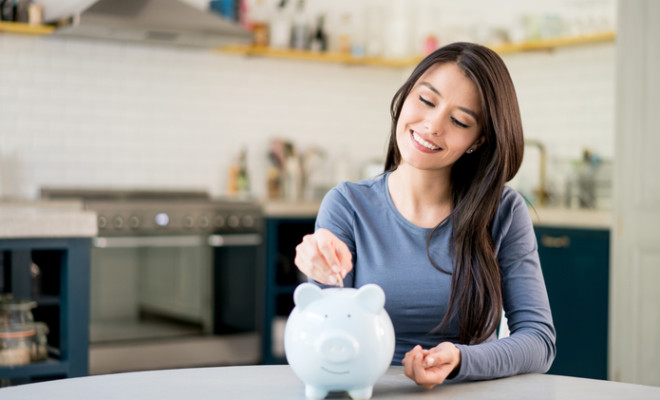 Portrait of a Latin American woman saving money in a piggybank and looking very happy