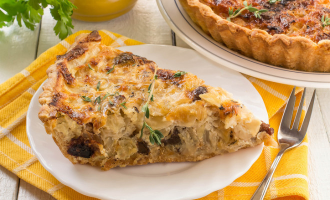 Delicious homemade quiche with cabbage and dried prunes. Vegetarian pie. Large pie and slice on plates, supplemented with fresh parsley and thyme, yellow napkin, white wooden table