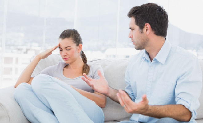 Man pleading with his upset partner on the couch at home in the living room