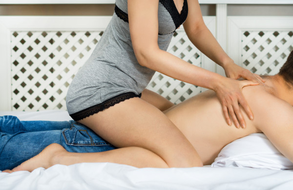 Woman making man erotic massage at home.
