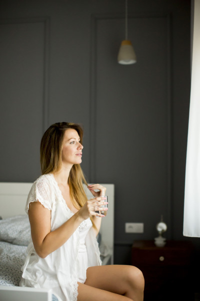 Woman drink a glass of water at morning after waking up