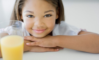 Smiling girl and glass of orange juice