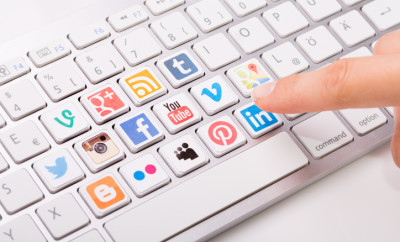 Belchatow, Poland - August 31, 2014: Male hand pointing on key with a social media logotype collection printed and placed on modern computer keyboard.