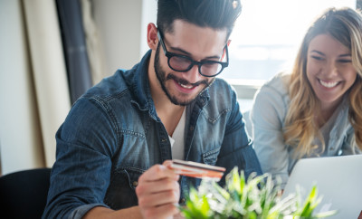 A happy young couple buying online with their credit card.