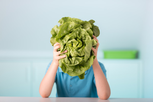 one 9 years old boy with green lettuce