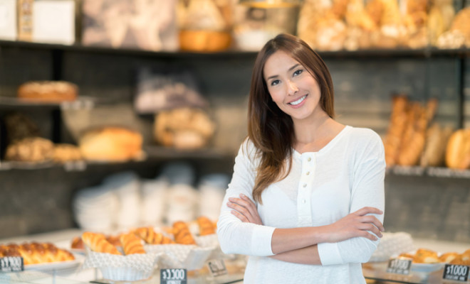 Happy client at a bakery looking at the camera smiling with arms crossed - small business concepts