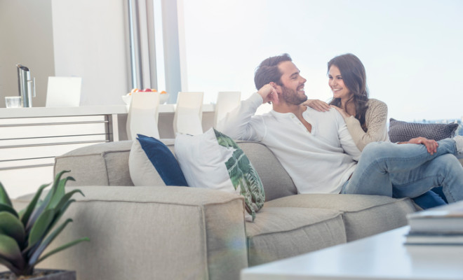 Couple relaxing on the sofa. They are cozy in a luxury home with views. Both are casually dressed. They are looking at camera, very happy and smiling