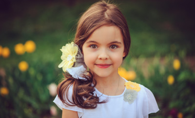 summer outdoor portrait of adorable smiling kid girl with yellow flowers on background