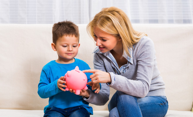 Happy mother and son are holding piggy bank.