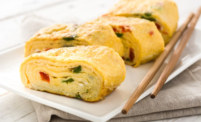 Traditional tamagoyaki Japanese omelette on white wooden table.