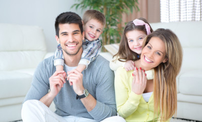 Happy family sitting on floor indoors. Smiling and looking at camera.