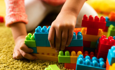Close-up of  little girl building something with plastic blocks on the floor.