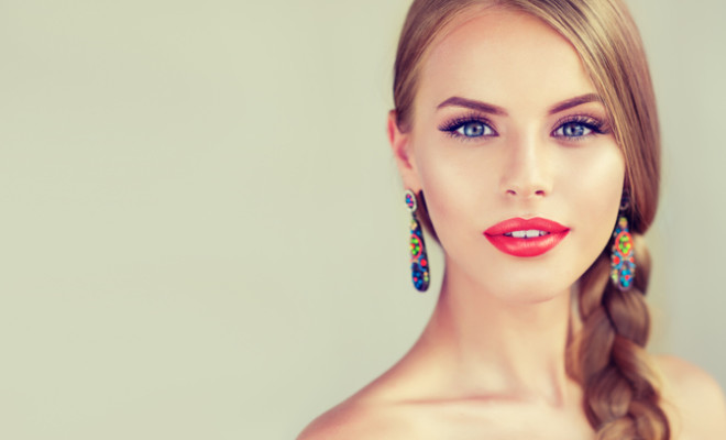 Close up portrait of beautiful young woman with braid(pigtail) and bright red lips . Fashion ,beauty and cosmetic.