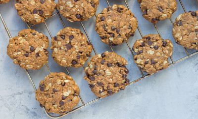 Flourless gluten free peanut butter, oatmeal and chocolate chips cookies on parchment, top view, copy space, horizontal