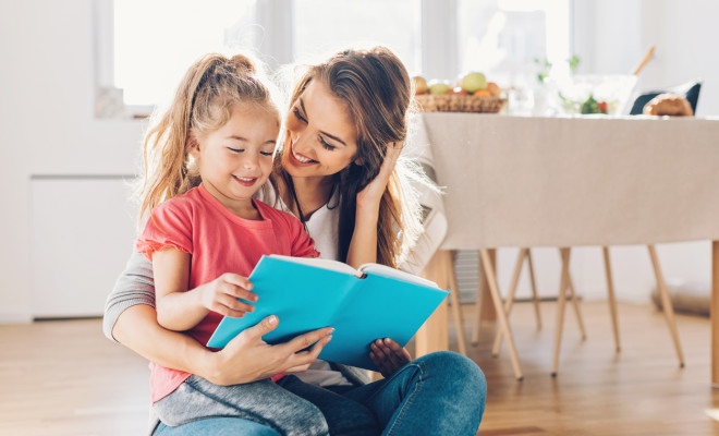 Mother and daughter reading book on the floor.