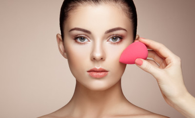 Makeup artist applies skintone. Beautiful woman face. Perfect makeup. Skincare foundation. Sponge makeup artist