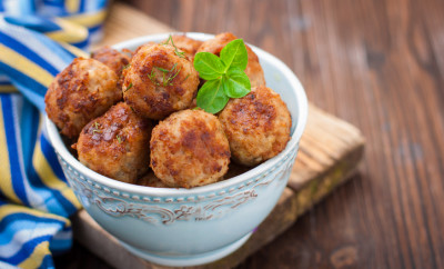 meatballs in a blue bowl on wooden table