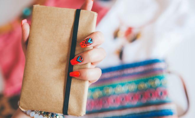 Female hand with stylish colorful boho nails holding notes
