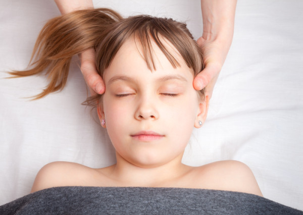 Girl receiving osteopathic treatment of her head