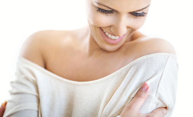 Closeup portrait of an attractive mid 30's woman gently hugging herself and smiling while looking down. Her head is slightly tilted, shot over white background.