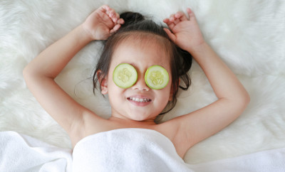 Cute little Child girl with a slice of cucumber in her eye, concept for skin care.