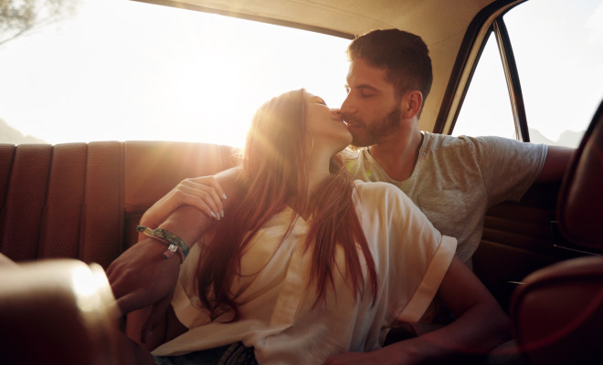 Romantic young couple sitting in back seat of a car and kissing . Affectionate couple on rear seat of a vehicle with sun flare.