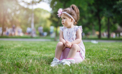 24 months old cute toddler girl is stopping to wear diapers, so potty is must have everywhere. She is urinating in a public park on a warm spring day.The emotion is real and candid because so is used to being photographed