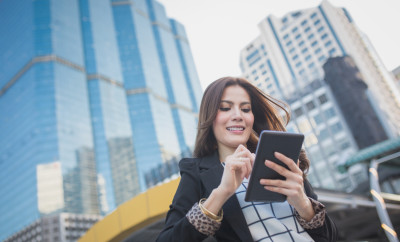 Portrait of successful smart business woman looking confident and smiling holding tablet computer