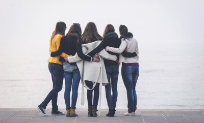 Group of female friends embracing by the sea on a foggy day