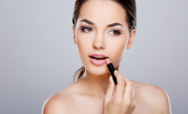 Beauty portrait of girl with perfect nude make-up. Painting lips with lipstick. Beauty salon. Head and shoulders, studio, indoors