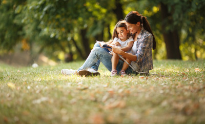 Mother and daughter relaxing in park.She reading a fairytale to her daughter