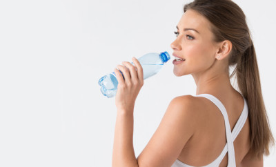 Beautiful fit woman drinking water from blue bottle on white background