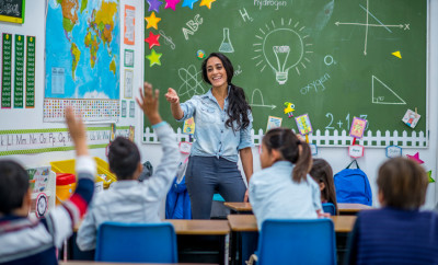 An Ethnic teacher is leading a class of elementary school children. There are various posters on the wall, and drawings on the chalkboard. Students are putting up their hands to answer a question.